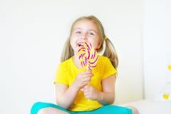 Смешная маленькая девочка есть большой леденец на палочке сахара Стоковая Фотография