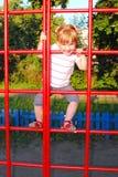 Смешная маленькая девочка играя на спортивной площадке. Стоковое Изображение RF