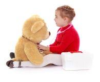 Смешная маленькая девочка играя доктора с плюшевым медвежонком Стоковая Фотография