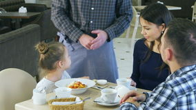 Смешная маленькая девочка играя с ее игрушкой перед едой ее обедающего в кафе с ее родителями Кельнер приносит ей штепсельную вил сток-видео