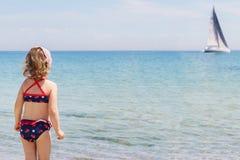 Смешная маленькая девочка смотря в расстояние на паруснике Стоковое Изображение