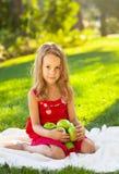 Смешная маленькая девочка с зелеными яблоками в парке лета Стоковая Фотография