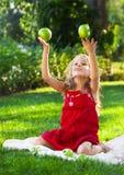 Смешная маленькая девочка с зелеными яблоками Стоковое Изображение RF