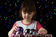 Смешная маленькая девочка с коробкой шариков рождества Стоковое Фото