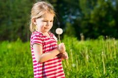 Смешная маленькая девочка с одуванчиком в ее руках делает желание Стоковые Фото