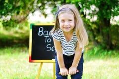 Смешная маленькая школьница чувствуя возбужденный о идти назад к школе Стоковое Изображение RF