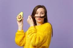 Смешная молодая женщина в свитере меха держа волосы как усик, держа наполовину свежего зрелого авокадоа изолированного на фиолете стоковые изображения