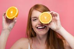 Смешная молодая женщина держа оранжевые куски на ее стороне и смотря камеру над розовой предпосылкой стоковое изображение rf