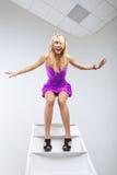 Смешная молодая женщина представляя на лестнице стоковые фото