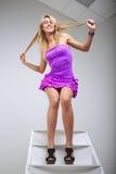 Смешная молодая женщина представляя на лестнице стоковая фотография