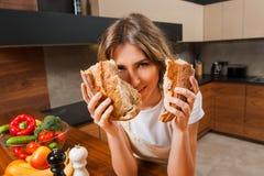 Смешная домохозяйка в кухне с свежим хлебом в руках стоковое изображение rf