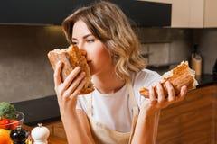 Смешная домохозяйка в кухне smeling свежий хлеб стоковая фотография rf