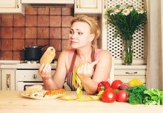 Смешная домохозяйка женщины выбирая между здоровой едой и быстрым foo Стоковое Изображение