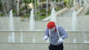 Смешная пантомима в красном берете играя рояль на предпосылке фонтана видеоматериал