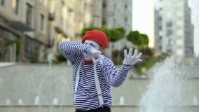 Смешная пантомима играя на скрипке на предпосылке фонтанов сток-видео