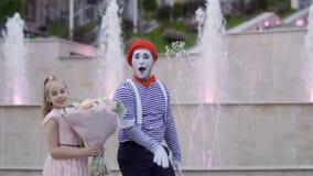 Смешная пантомима и маленькая девочка с букетом цветков на предпосылке фонтанов видеоматериал