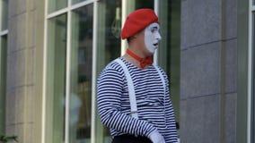 Смешная пантомима смотря окно офиса и связывает с людьми сток-видео