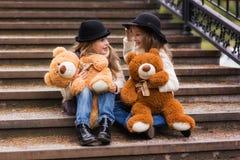 Смешная подруга девушки сидя на лестницах с нежностью забавляется в парке Стоковые Фотографии RF