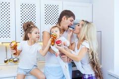 Смешная семья из четырех человек на предпосылке яркой кухни красивой имеет потеху околпачивая вокруг есть donuts Концепция  Стоковые Изображения