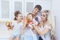 Смешная семья из четырех человек на предпосылке яркой кухни красивой имеет потеху околпачивая вокруг есть donuts Концепция  Стоковая Фотография RF