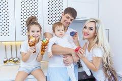 Смешная семья из четырех человек на предпосылке яркой кухни красивой имеет потеху околпачивая вокруг есть donuts Концепция  Стоковая Фотография
