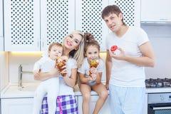 Смешная семья из четырех человек на предпосылке яркой кухни красивой имеет потеху околпачивая вокруг есть donuts Концепция  Стоковое Изображение RF