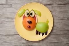 Смешная собака плодоовощ на плите и деревянной предпосылке Стоковые Фотографии RF