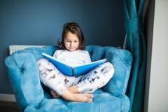 Смешная счастливая маленькая девочка читая книгу и играя в кровати Игра детей дома Белый питомник Ребенок в солнечной спальне дет Стоковое фото RF