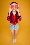 Смешная счастливая молодая женщина с половинами грейпфрута над глазами Стоковые Изображения