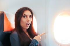 Смешная удивленная женщина сидя окном на самолете стоковое изображение
