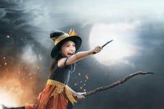 Смешное азиатское летание девушки ребенка на broomstick Стоковое Изображение