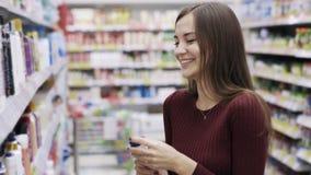 Смешное видео, женщина принимает гель ливня, обнюхивает его и смеется в отделе косметик супермаркета видеоматериал
