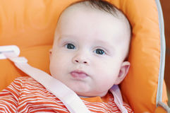 Смешное время младенца 5 месяцев сидя на высоком стульчике Стоковое Фото