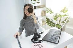 Смешное изображение девушки сидя на таблице в большой светлой комнате и записывая видео Она смотрит к видеокамере Стоковые Фотографии RF