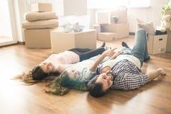 Смешное изображение семьи лежа на поле в их собственной новой квартире Они имеют много потеху совместно Также они стоковое фото rf