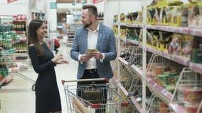 Смешное положительное видео молодых пар делая ежедневное приобретение на супермаркете видеоматериал
