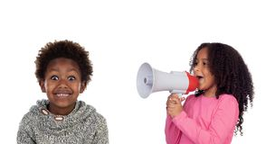 Смешное childr крича через мегафон к его брату стоковое изображение