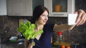 Смешное selfie всхода домохозяйки женщины с зеленым салатом пока варящ в кухне дома внутри помещения Стоковое Изображение