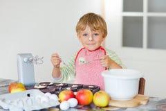 Смешной белокурый торт яблока выпечки мальчика ребенк внутри помещения Стоковое Фото