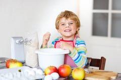 Смешной белокурый торт яблока выпечки мальчика ребенк внутри помещения Стоковое Изображение