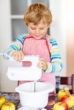 Смешной белокурый торт яблока выпечки мальчика ребенк внутри помещения Стоковые Изображения
