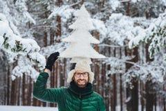 Смешной бородатый мужчина с бородой, одетой в теплых одеждах зимы, держит искусственную ель на голове, представлениях против дере стоковые изображения rf