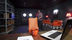 Смешной бородатый парень нося солнечные очки активно танцует в комнат видеоматериал