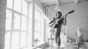 Смешной бородатый танец человека на кровати поя и играя электрическую гитару в спальне дома Стоковая Фотография