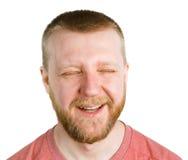 Смешной бородатый человек с сужанными глазами стоковые изображения rf