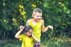Смешной брат и сестра играя в лете идут дождь Стоковые Изображения RF