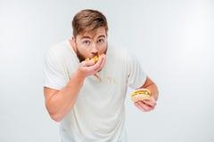 Смешной голодный бородатый человек есть высококалорийную вредную пищу стоковое фото rf