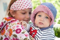Смешной жизнерадостный младенец outdoors с обнимать ее сестру символизируя единение и счастье Стоковая Фотография RF