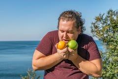Смешной жирный человек на океане есть плоды Каникулы, потеря веса и здоровая еда стоковая фотография rf