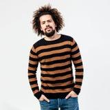 Смешной курчавый парень с бородой одетой в striped черных и желтых представлениях свитера и джинсов в студию на белизне стоковая фотография rf